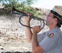 "Gregory Cunningham, park ranger plays ""Taps"" at a Memorial Day service at Pu'ukohola Heiau National Historic Park on May 25.  (PHOTO BY LISA MARIE DAHM 